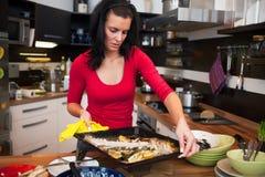 La mujer hace la limpieza en cocina Imagenes de archivo