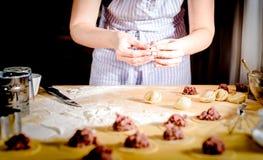 La mujer hace las bolas de masa hervida en casa en la tabla de cocina, cierre para arriba Fotos de archivo libres de regalías