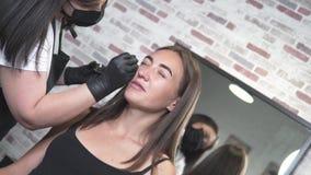 La mujer hace las cejas brillantes con el salón de belleza almacen de metraje de vídeo