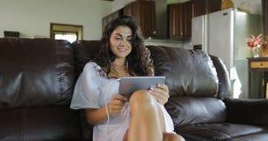 La mujer hace llamada video en línea usando el sitio de Sit On Coach In Living de la tableta, Internet de discurso sonriente de l almacen de video