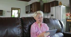 La mujer hace llamada video en línea usando el sitio de Sit On Coach In Living de la tableta, Internet de discurso sonriente de l almacen de metraje de vídeo