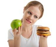 La mujer hace los alimentos de la opción, sanos y malsanos Imágenes de archivo libres de regalías