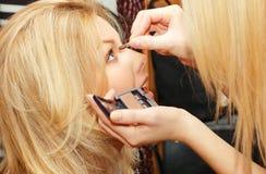 La mujer hace maquillaje fotos de archivo