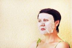 La mujer hace procedimientos cosméticos faciales Fotografía de archivo libre de regalías