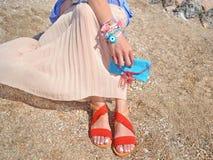 La mujer hace publicidad de los accesorios hechos a mano en la playa Fotografía de archivo libre de regalías