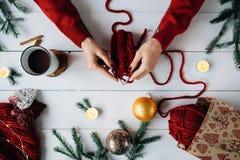 La mujer hace punto cosas de la Navidad en el fondo de madera blanco Imágenes de archivo libres de regalías