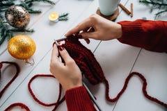 La mujer hace punto cosas de la Navidad en el fondo de madera blanco Fotografía de archivo libre de regalías