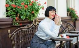 La mujer hace que la bebida goce el leer de la buena terraza del caf? del libro Literatura moderna para la hembra Caf? y buen lib imagenes de archivo