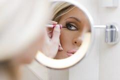La mujer hace un maquillaje Imágenes de archivo libres de regalías
