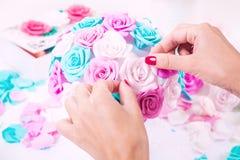 La mujer hace un ramo de flores artificiales Imágenes de archivo libres de regalías