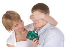 La mujer hace un regalo al marido Foto de archivo