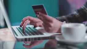 La mujer hace una compra en línea con una tarjeta de crédito y un ordenador portátil