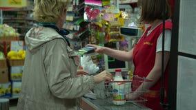 La mujer hace una compra en la tienda por la tarjeta de crédito almacen de metraje de vídeo