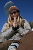 la mujer hermosa activa con un snowboard ruega Fotografía de archivo libre de regalías