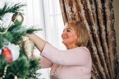 La mujer hermosa adorna el árbol de navidad Imagen de archivo libre de regalías