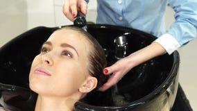 La mujer hermosa alegre que le conseguía el pelo se lavó por un peluquero en el salón fotografía de archivo libre de regalías