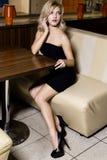 La mujer hermosa alegre se sienta en el café antes de fecha Imagenes de archivo