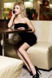 La mujer hermosa alegre se sienta en el café antes de fecha Fotos de archivo