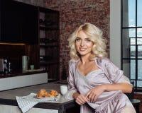 La mujer hermosa atractiva en pijamas de seda rosados desayuna en casa en cocina imagenes de archivo