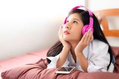 La mujer hermosa atractiva es música que escucha usando Bluetooth y conecta con el smartphone La mujer asiática hermosa encantado imagenes de archivo