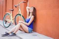 La mujer hermosa atractiva que se sienta cerca de la pared y el vintage montan en bicicleta Imagen de archivo