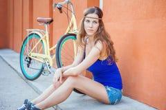 La mujer hermosa atractiva que se sienta cerca de la pared y el vintage montan en bicicleta Imágenes de archivo libres de regalías