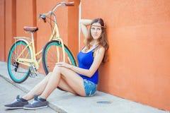 La mujer hermosa atractiva que se sienta cerca de la pared y el vintage montan en bicicleta Fotografía de archivo