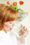 La mujer hermosa bebe el agua Fotos de archivo libres de regalías