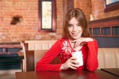 La mujer hermosa bebe té en café. Imagen de archivo libre de regalías