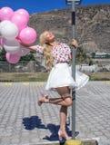 La mujer hermosa, blonde se está colocando en posts de la lámpara y sostiene muchos globos foto de archivo