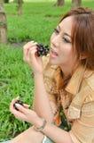 La mujer hermosa come la fruta Foto de archivo