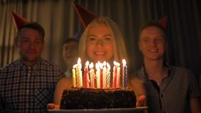 La mujer hermosa comparte la celebración del cumpleaños con los amigos recolectados soplando hacia fuera velas en la torta almacen de metraje de vídeo