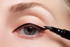 La mujer hermosa con brillante compone el ojo con maquillaje del trazador de líneas del negro sexy Forma de la flecha de la moda  Foto de archivo libre de regalías