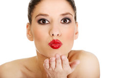 La mujer hermosa con compone soplar un beso Imagenes de archivo