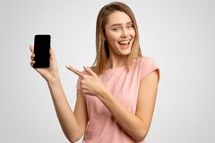 La mujer hermosa con el dedo índice muestra a pantalla en blanco del teléfono donde usted puede colocar su anuncio La chica joven fotografía de archivo