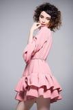 La mujer hermosa con el estilo de pelo afro que lleva un vestido rosado riza Imagen de archivo
