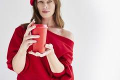 La mujer hermosa con el pelo largo que lleva el sombrero y el suéter rojos sostiene la taza de café disponible de papel Espacio p imagen de archivo libre de regalías