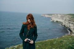 La mujer hermosa con el pelo rojo largo sostiene la cámara al borde de la montaña cerca del mar fotos de archivo libres de regalías