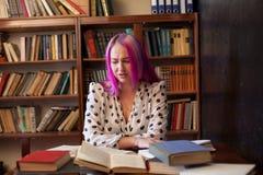 La mujer hermosa con el pelo rosado lee los libros en la biblioteca imágenes de archivo libres de regalías