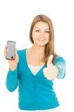 La mujer hermosa con el teléfono muestra golpe para arriba Foto de archivo libre de regalías