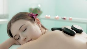 La mujer hermosa con la flor es goce de efectos terapéuticos de un masaje de piedra caliente tradicional en el balneario y la sal metrajes