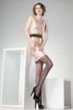 La mujer hermosa con las piernas atractivas largas vistió la presentación elegante en el estudio - cuerpo completo imagenes de archivo