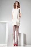 La mujer hermosa con las piernas atractivas largas vistió la presentación elegante en el estudio - cuerpo completo fotografía de archivo