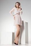 La mujer hermosa con las piernas atractivas largas vistió la presentación elegante retra en el estudio Imágenes de archivo libres de regalías