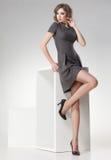 La mujer hermosa con las piernas atractivas largas vistió la presentación elegante retra en el estudio Imagen de archivo