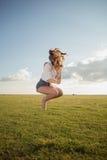 La mujer hermosa con las piernas y el dril de algodón atractivos pone en cortocircuito el salto en la hierba, zapato menos Fotos de archivo