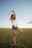 La mujer hermosa con las piernas y el dril de algodón atractivos pone en cortocircuito en la hierba, zapato menos Imagen de archivo