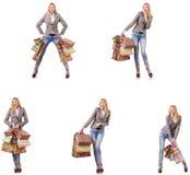La mujer hermosa con los bolsos de compras aislados en blanco imagen de archivo