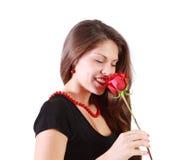 la mujer hermosa con los ojos cerrados huele la rosa del rojo Fotografía de archivo