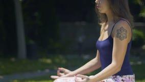 La mujer hermosa con los tatuajes se sienta en la actitud del loto que medita profundamente el parque del aire libre almacen de video
